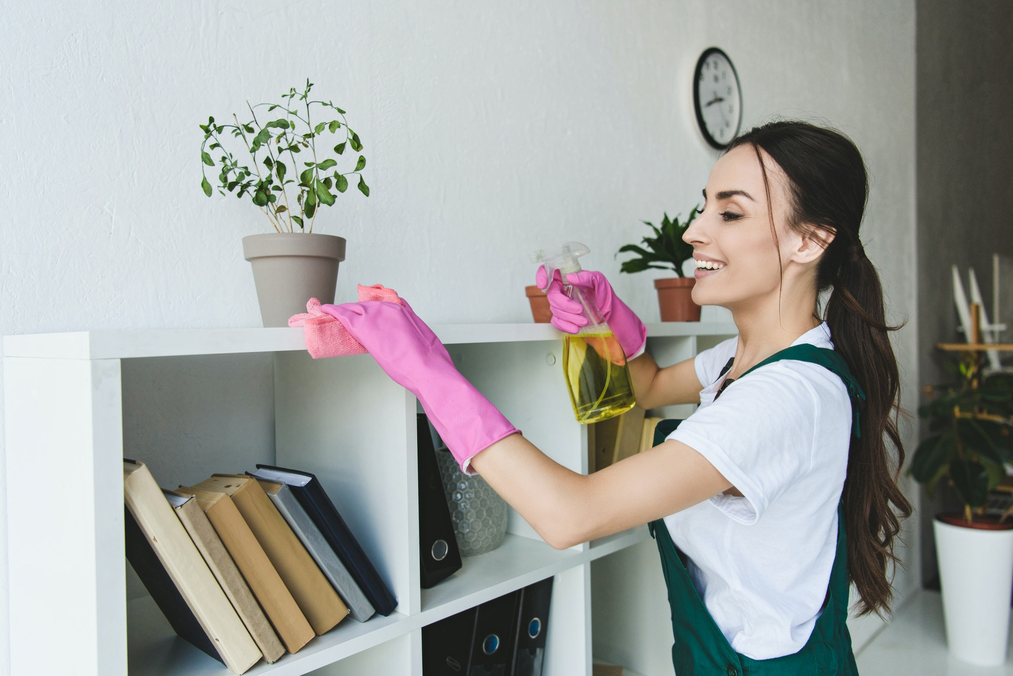 smiling young woman in rubber gloves cleaning shelves in office