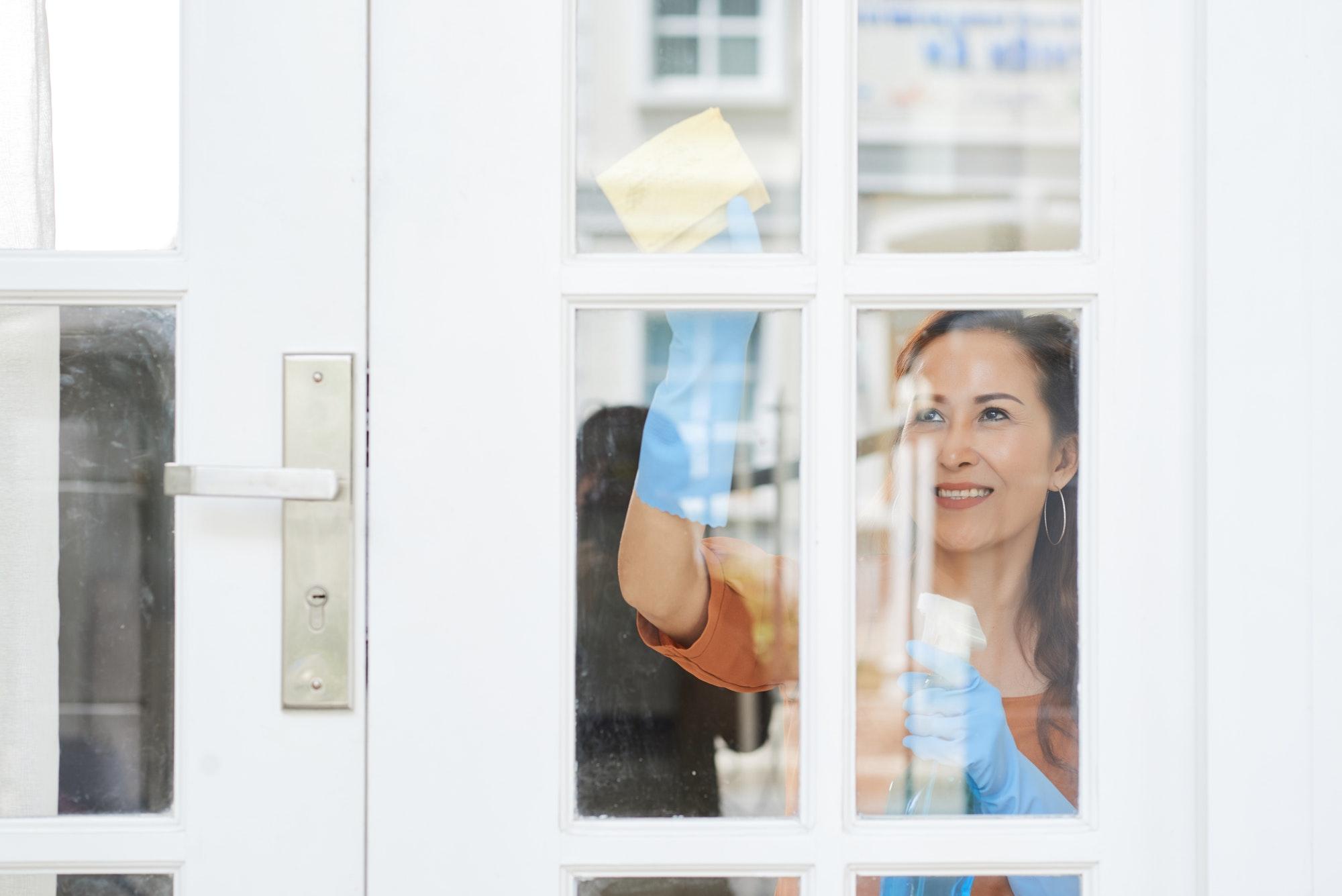 Housewife cleaning door
